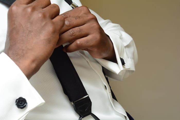 Groom fastens his suspenders for tuxedo