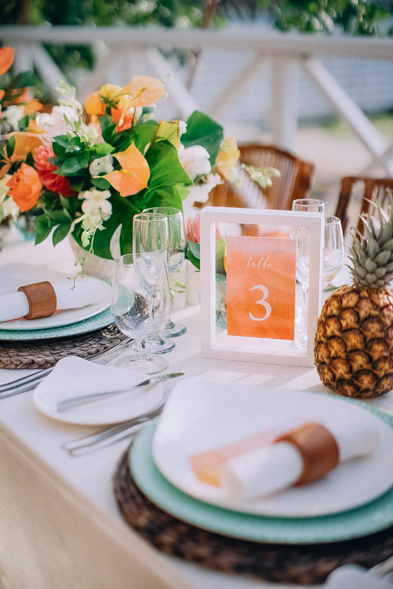 Light cyan flowers and miniature pineapples line the table for a tropical feel.