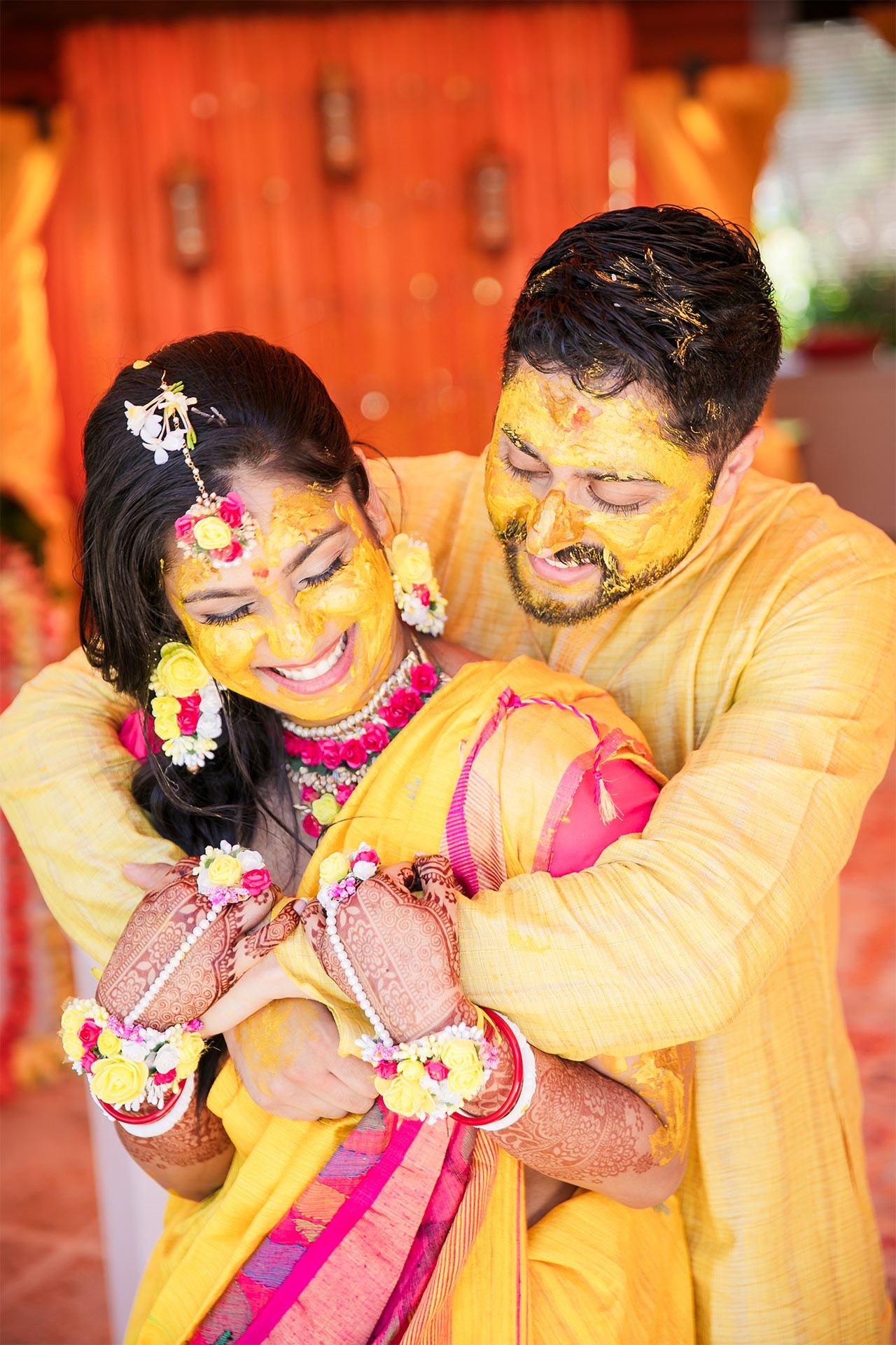 Bride and Groom covered in Haldi surrounded by orange and yellow fabrics
