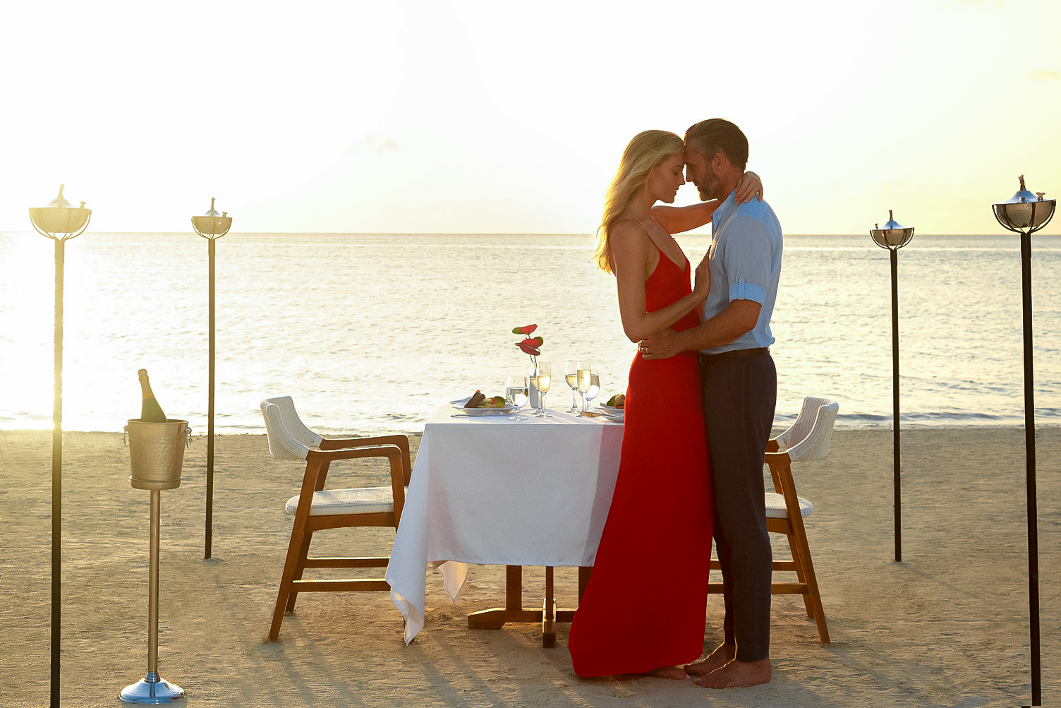 Couple enjoys private candlelit dinner beside the sea