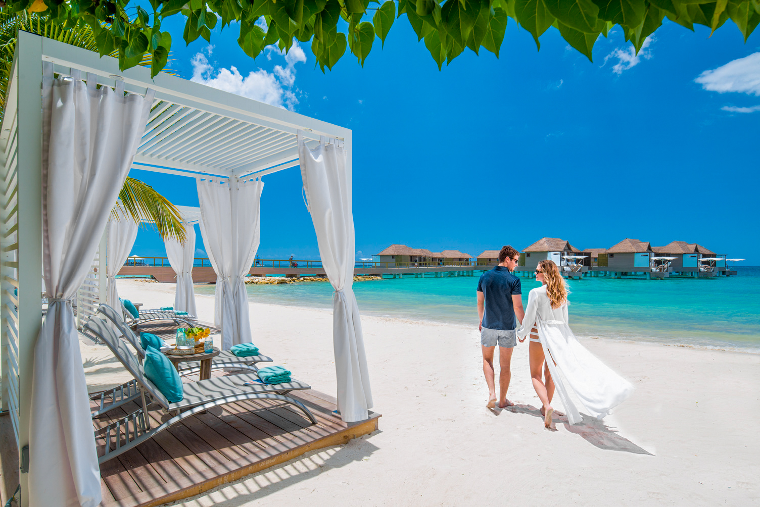 Couple walks along a quiet, white sand beach