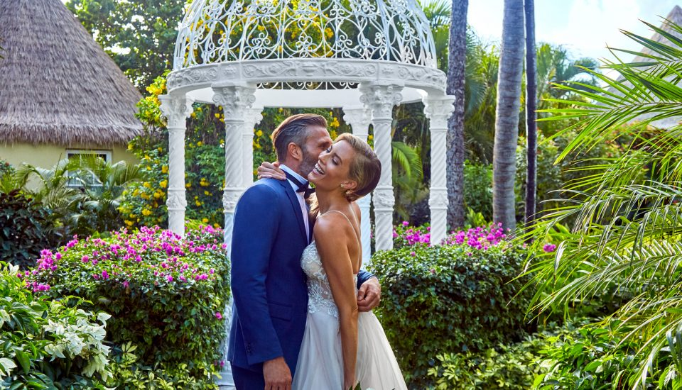 Bride and groom surrounded by foliage and a quiet gazebo