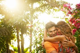 Couple embracing in.a tropical garden setting during golden hour