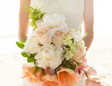 Bride holding bouquet of pink, coral, white, and subtle green wedding florals.