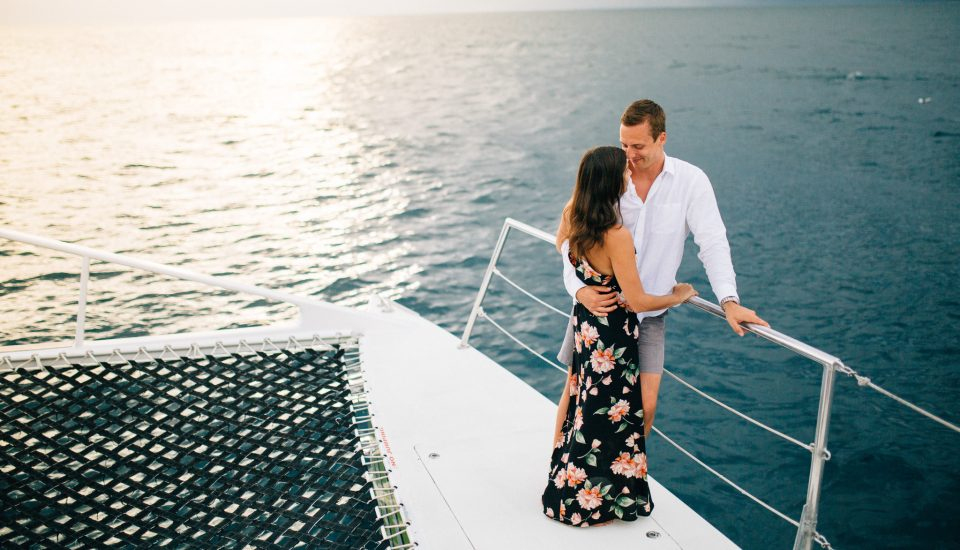 Real love stories. Pictured: Couple embracing on a boat, surrounded by the Caribbean Sea.