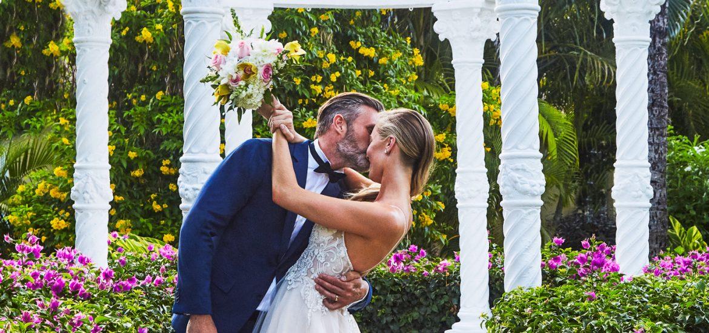 Bride and groom under garden gazebo