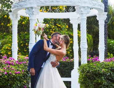 Bride and groom under garden gazebo