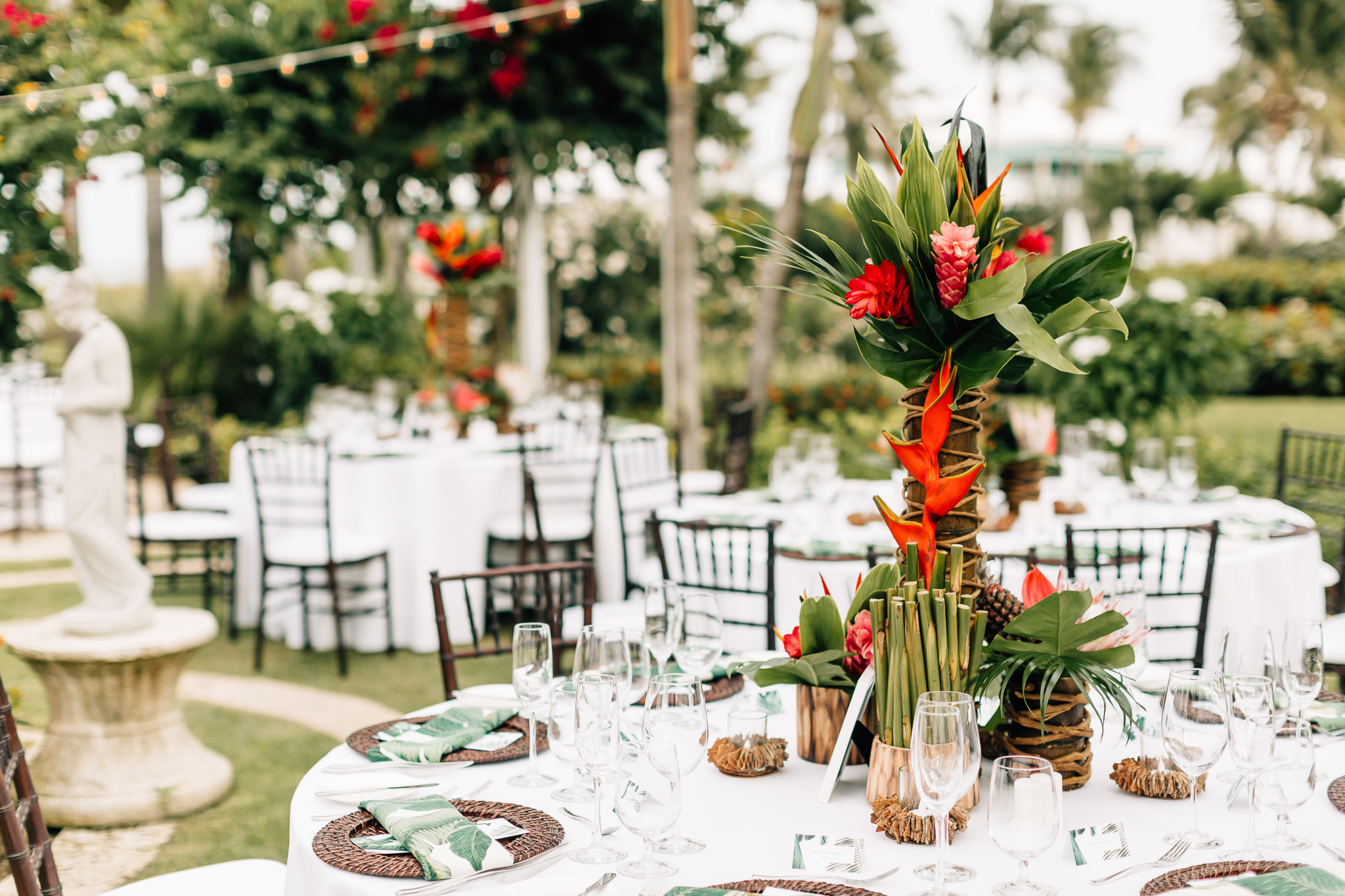A tropical reception centerpiece featuring bursts of red wedding florals and touches of deep green palm leaves.