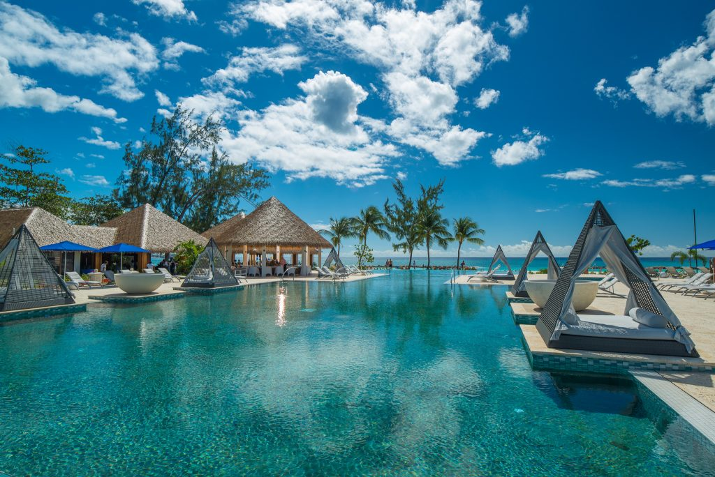 Expansive main pool at Sandals Royal Barbados with ocean views and modern day beds for lounging.