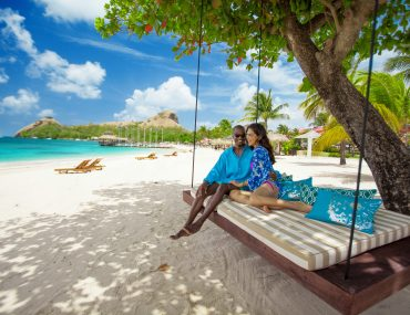 Couple sitting on swing beneath a tree looking out at the Caribbean Sea