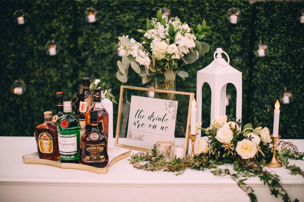 Custom signage and assortment of top-shelf liquors surrounded. by green florals