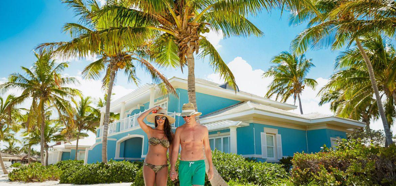 Couples walks beneath lush palm trees and the Caribbean sun during a WeddingMoons Reunion.