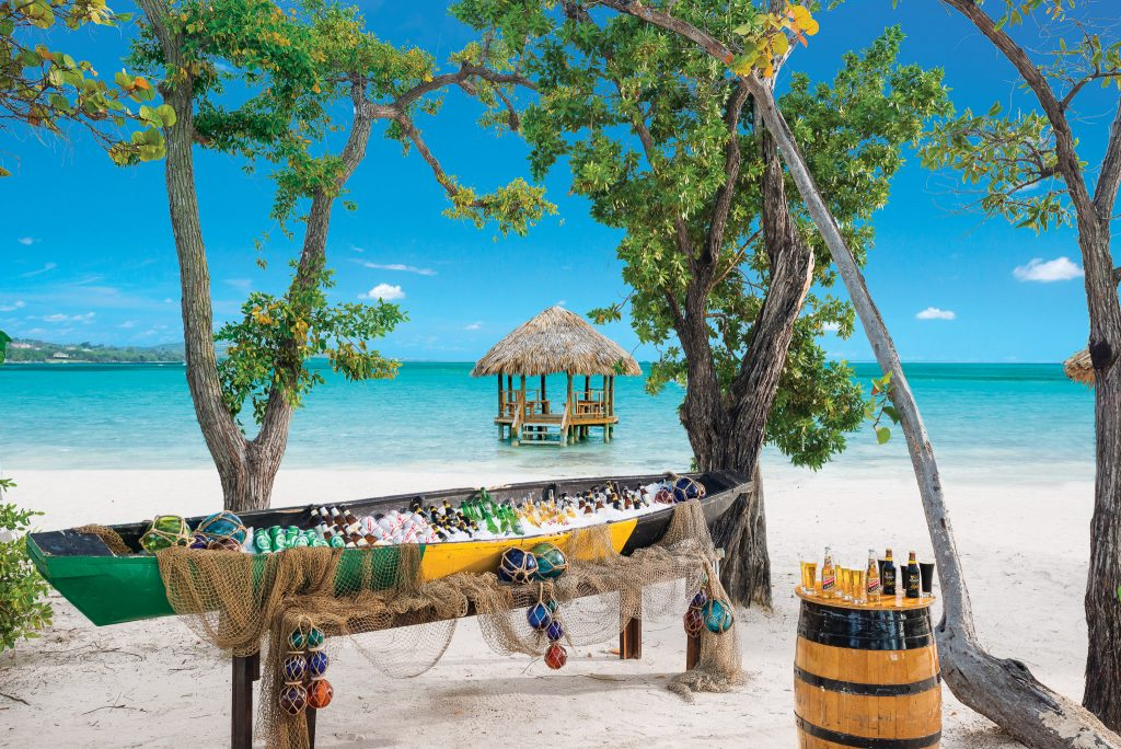 Beer canoe sits on a white-sand beach with turquoise waters in the background