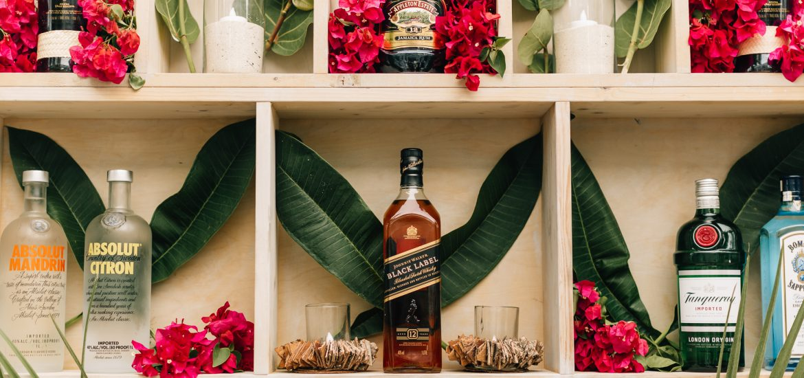 Florals and bottles of premium liquor make up this wedding bar
