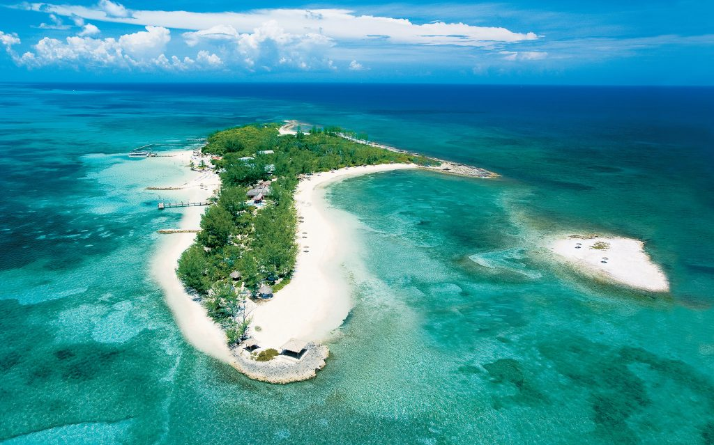 Private offshore island surrounded by emerald, turquoise and sapphire waters.