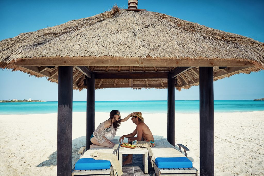 Couple under beachfront cabana during destination mini-moon