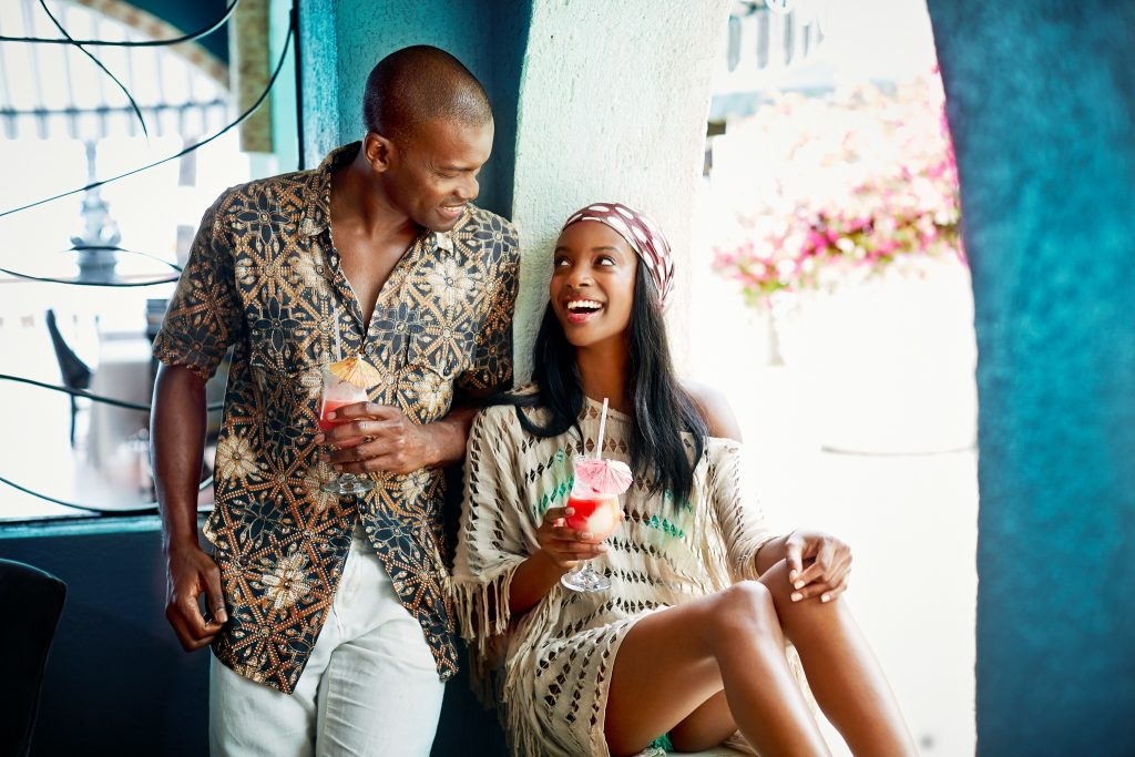 Couple share a happy moment over all-inclusive cocktails