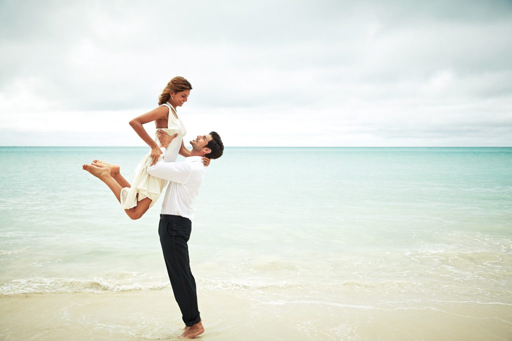 Groom lifts bride at the ocean's edge.