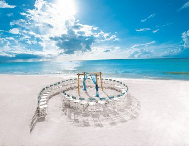 Beachfront destination wedding location depicts a ceremony setup with chair arranged like a seashell