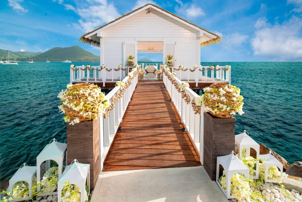 Bridge leading up to an over-the-Water wedding chapel, surrounded by blue waters and mountains looking on in the background.