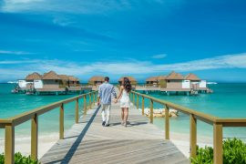 Couple walking hand-in-hand to Sandals signature Over-the-Water Butler Bungalows and Villas