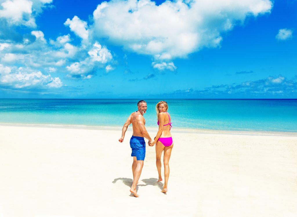 Couple walks toward crystal blue waters on a white sand beach