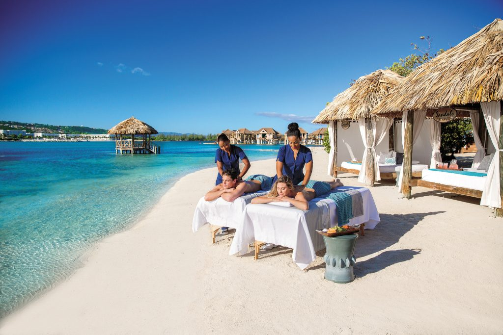 Couple getting a massage on the beach, next to the ocean.