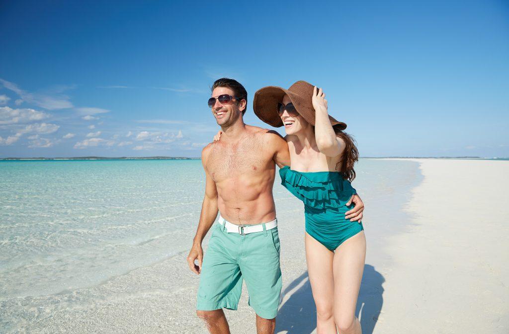 Couple enjoys a stroll down the beach on a sunny day.