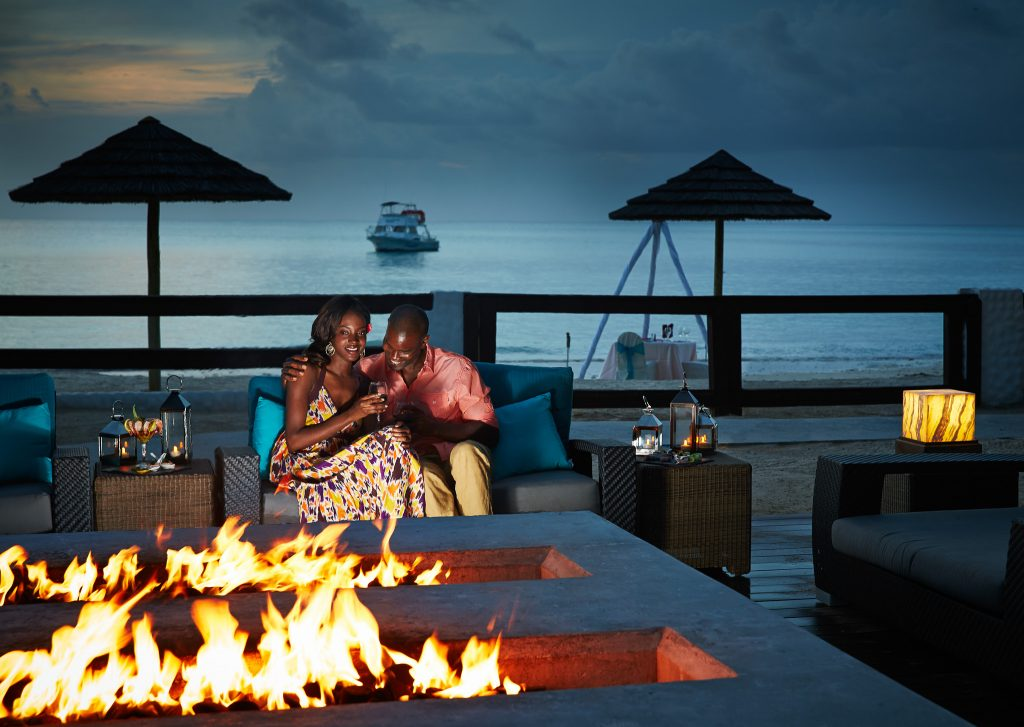 Fire pits are among the best honeymoon ideas for newlyweds! The couple pictured shares a romantic moment, fireside, with wine glasses in hand.