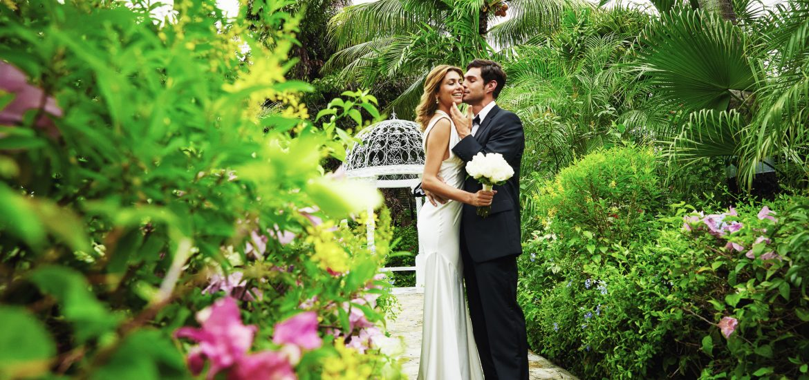Bride and groom standing in a lush garden setting for photos captured by a destination wedding photographer