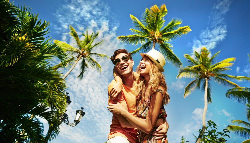Couple laughing and hugging beneath tropical palms