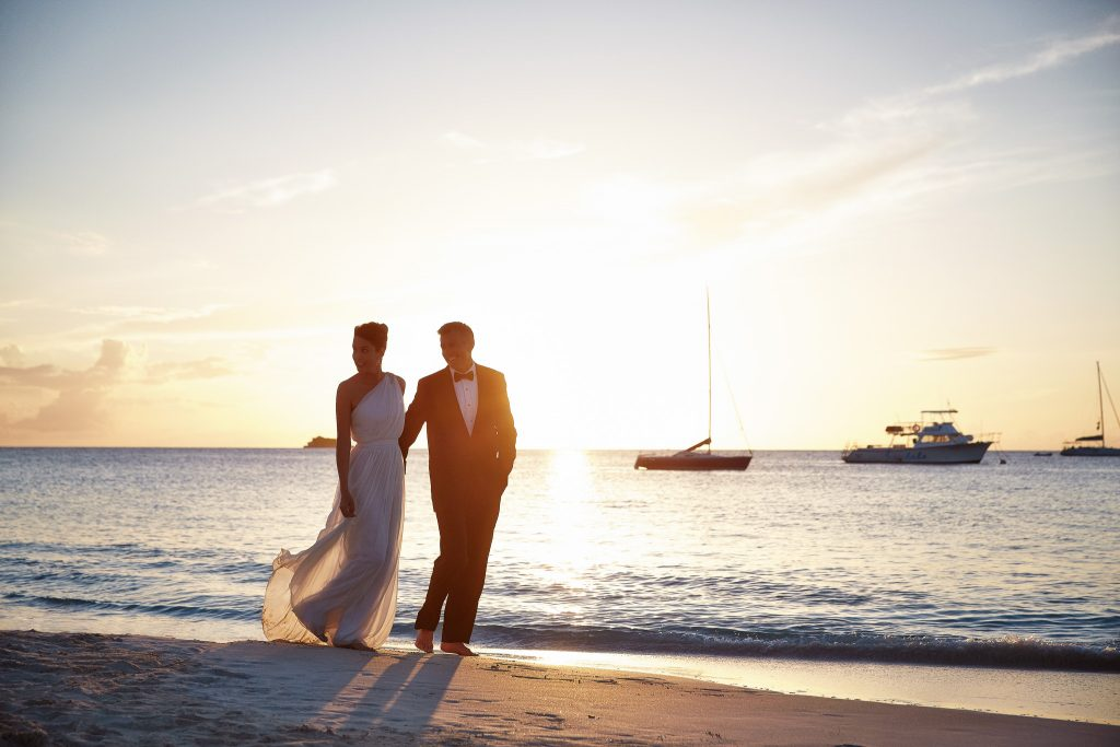 Bride and groom walking down the beach at sunset.