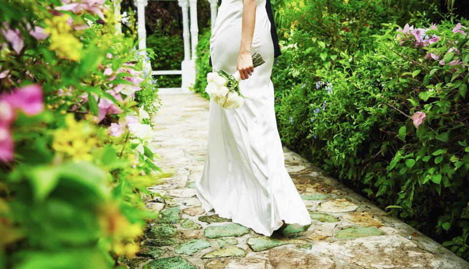 Bride walking through a lush garden, holding a posy wedding bouquet.